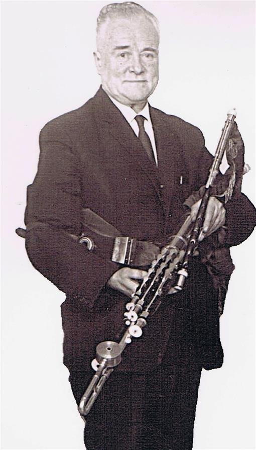 Leo Rowsome standing with Uileann pipes